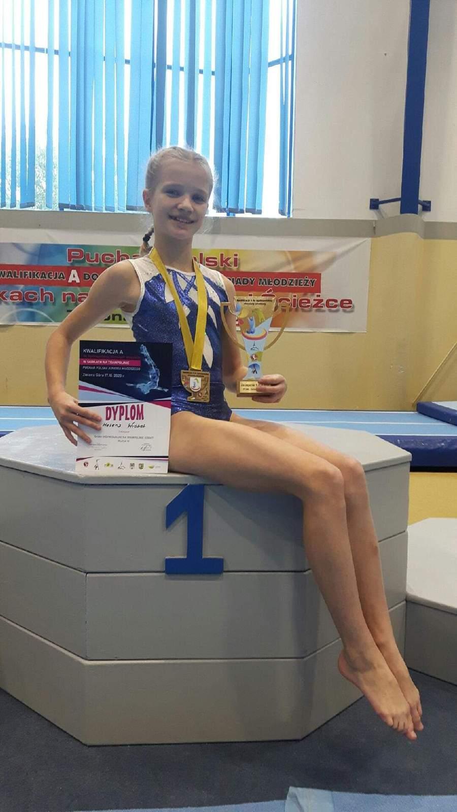 Dziewczynka siedzi na podium. Na szyi ma zawieszony złoty medal, w rękach trzyma statuetkę i pamiątkowy dyplom.