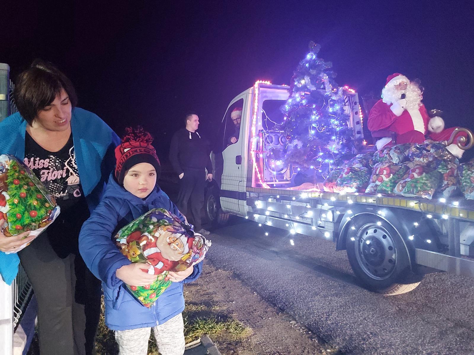 Dziecko odebrało prezent od św. Mikołaja, w tle orszak świętego