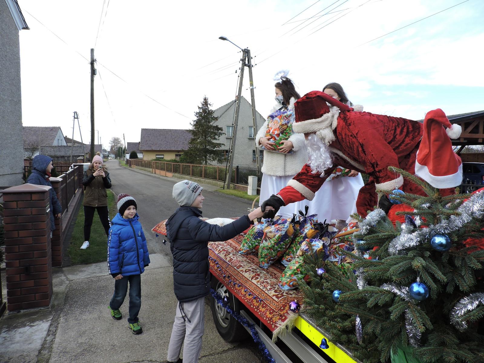 Orszak w Biadaczu - dziecko odbiera prezent od św. Mikołaja