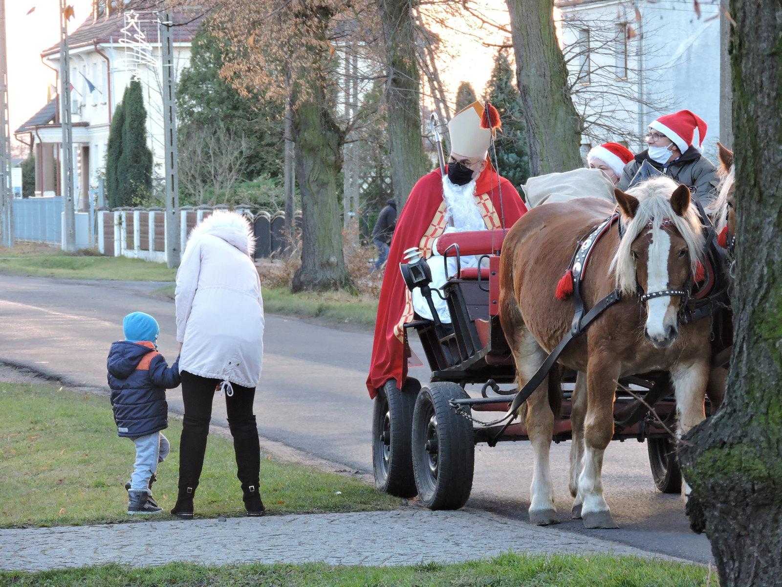 Dziecko odbiera prezent przy bryczce, na której siedzi św. Mikołaj
