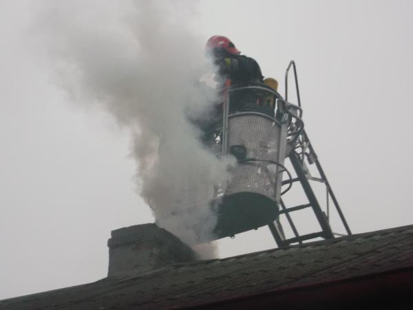 Strażak gasi pożar w kominie