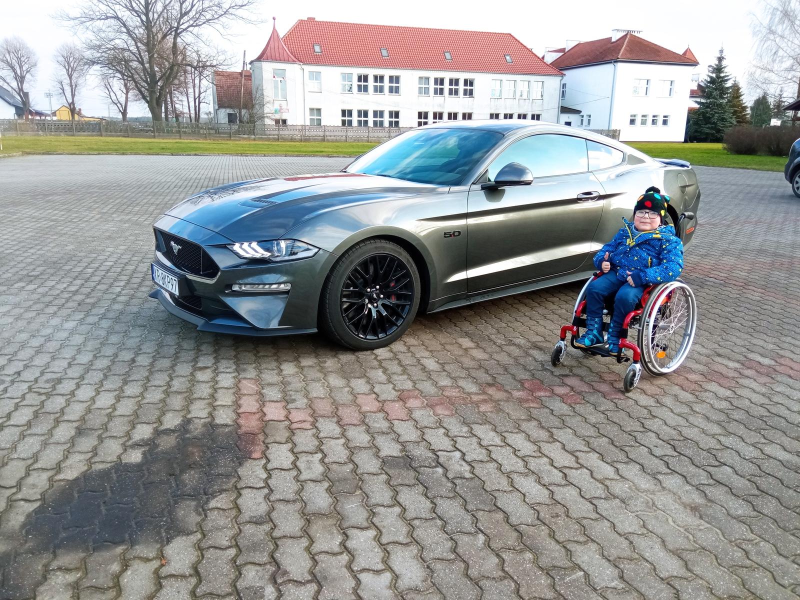 Szymonek przed samochodem marki Mustang na parkingu przed Łubniańskim Ośrodkiem Kultury