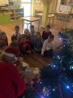 Przedszkolaki z Kępy siedzą wokół prezentu, przy choince