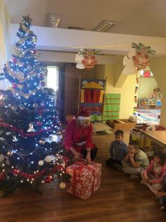 Dyrektor Przedszkola w Kępie otwiera prezent pod choinką