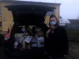 Ewa Moczko przy samochodzie z otwartym bagażnikiem, w którym są prezenty dla DPS w Gierałcicach