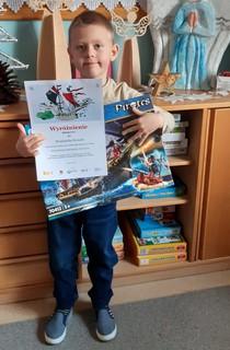 Wojciech Symala trzyma w rękach dyplom oraz klocki - nagrodę w konkursie