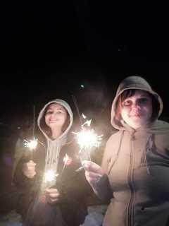 Dwie kobiety trzymają w rękach odpalone zimne ognie