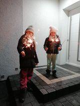 Dzieci przed domem trzymają odpalone zimne ognie
