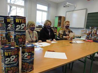 Puszki WOŚP, za nimi osoby czekające na wolontariuszy WOŚP w siedzibie sztabu w Brynicy