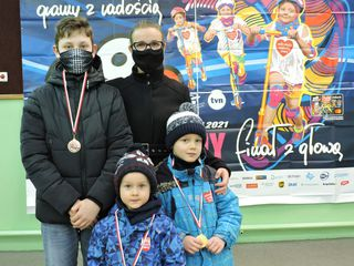 """Kobieta i trójka dzieci prezentują medale po ukończeniu biegu """"Rusz się dla serca"""""""