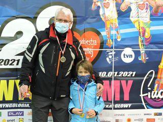 Mężczyzna z dzieckiem prezentują medale po zakończeniu biegu