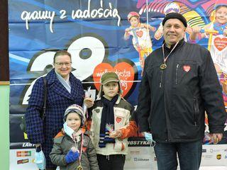 Dwóch dorosłych i dwoje dzieci prezentują medale otrzymane po uczestnictwie w biegu