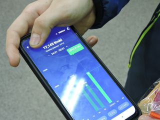 Na zdjęciu telefon z ekranem aplikacji mobilnej, na której widać pokonany dystans