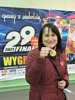 """Uczestniczka biegu """"Rusz się dla serca"""" pokazuje zdobyty medal"""