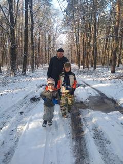 Mężczyzna i dwójka dzieci w trakcie spaceru w lesie