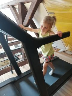 Dziewczynka w trakcie aktywności fizycznej na bieżni stacjonarnej